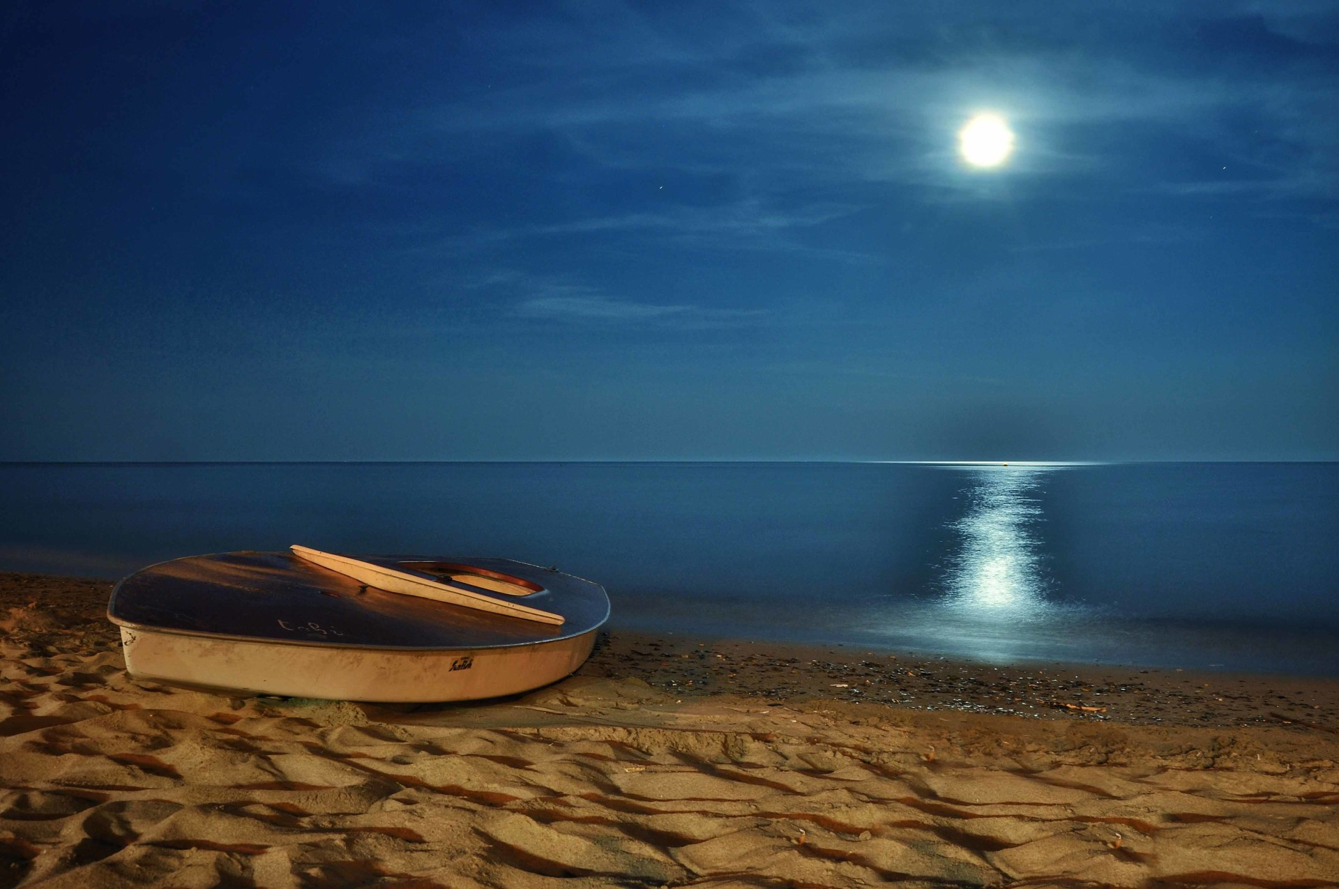 moon lighting small boat on the beach